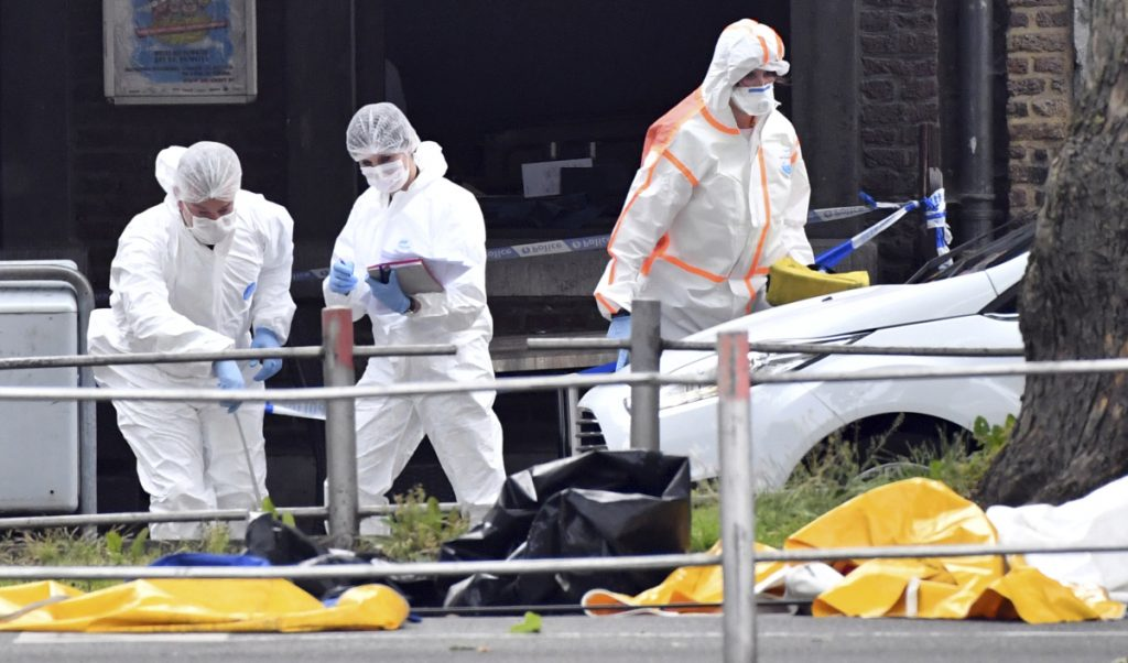 Forensic police investigate at the scene of a shooting in Liege, Belgium on Tuesday. A gunman killed three people, including two police officers a city official said. Police later killed the attacker.