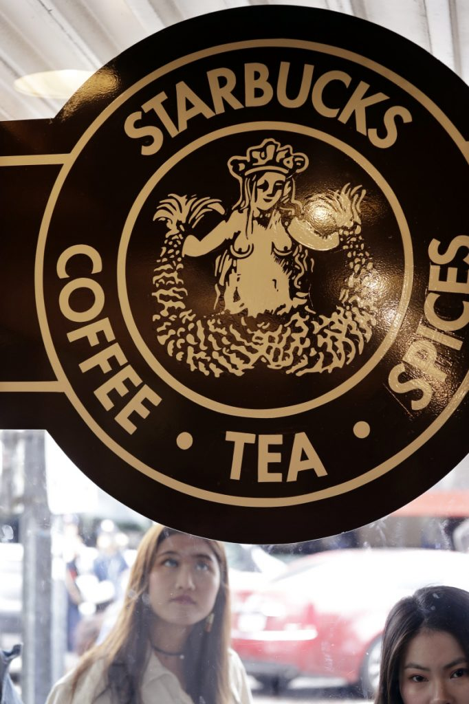 Visitors peer inside the 'original' Starbucks in Seattle shortly before it closed for bias training on Tuesday.