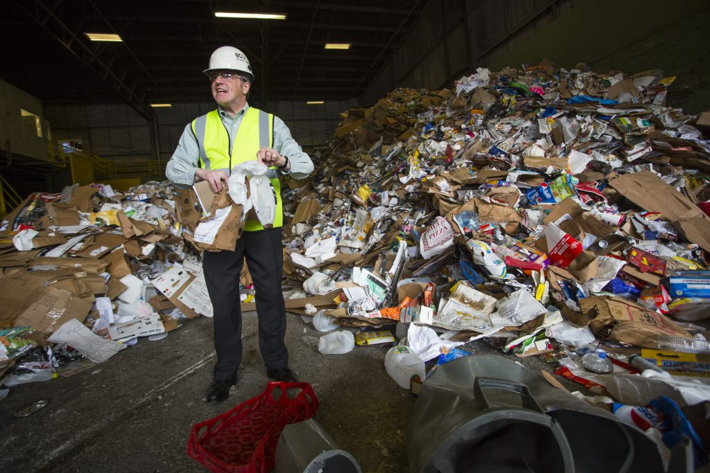 "Ecomaine CEO Kevin Roche picks through unsorted materials. ""The only variable we can do something about is contamination,"" Roche said. ""We need everyone's help to fix this problem. The next time you go to a recycling bin, ask yourself 'which bin should I put this in?' If you don't know, please find out."""