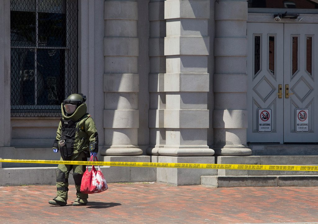 A bomb squad technician removes a suspicious bag after X-raying it on Wednesday in the Old Port. The bag was left on the corner of Pearl and Commercial streets, in front of the U.S. Custom House.