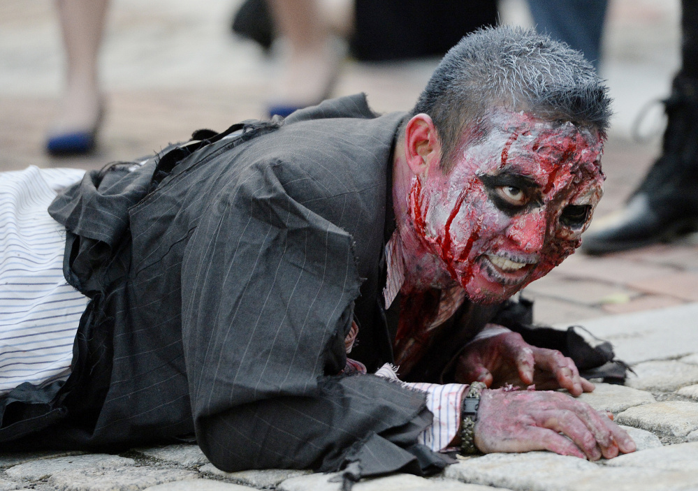 Brian Noyes of Portland  crawls through Monument Square as he performs during a zombie dance event in October 2015.