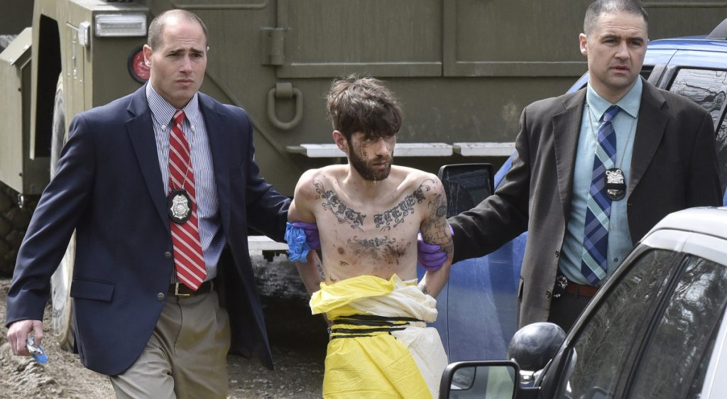 Suspected police-killer John Williams is led by Maine State Police detectives to a cruiser after being arrested Saturday in Fairfield, following a four-day manhunt after he allegedly shot Cpl. Eugene Cole, of the Somerset County Sheriff's Office.