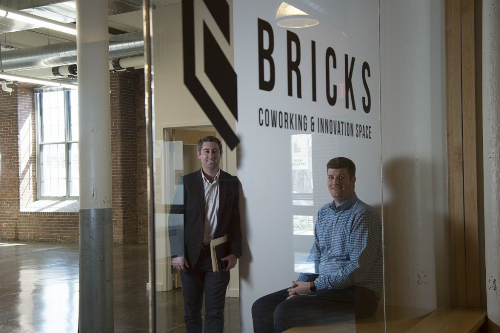 Garvan Donegan, an economic development specialist for the Central Maine Growth Council, center, and RJ Anzelc, founder of Bricks Coworking & Innovation Space and a software developer and entrepreneur, pose for a portrait Wednesday at a new rental office space at the Hathaway Center in Waterville.
