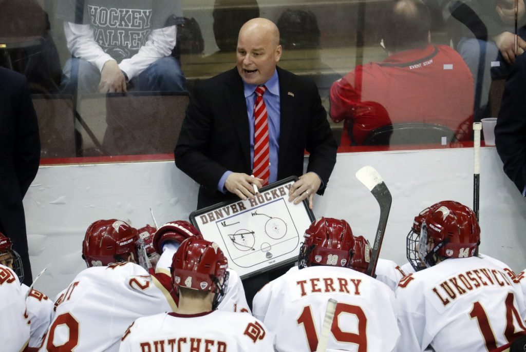 In this March 2017 photo, Denver head coach Jim Montgomery directs his players during a time-out in the second period of the midwest regional final of the NCAA hockey tournament in Cincinnati. A person with knowledge of the situation tells The Associated Press that the Dallas Stars will hire Montgomery to be their next head coach. Montgomery takes over Ken Hitchcock, who retired last month and will become a consultant for the Stars. The person spoke on condition of anonymity Wednesday because the hiring had not been announced.