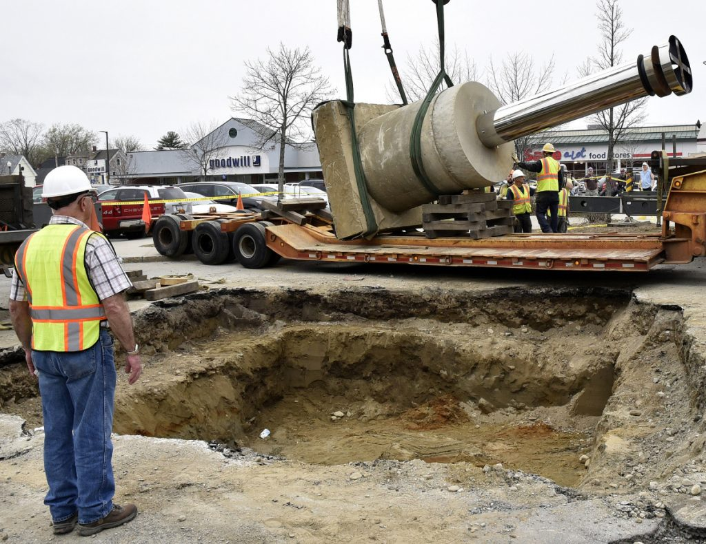 "Waterville Public Works Director Mark Turner stands beside a gaping hole Thursday, May 3, in The Concourse in Waterville as a crane crew slowly lowers the base of ""The Ticonic"" sculpture onto a trailer that later carried the piece to its new site at Head of Falls."