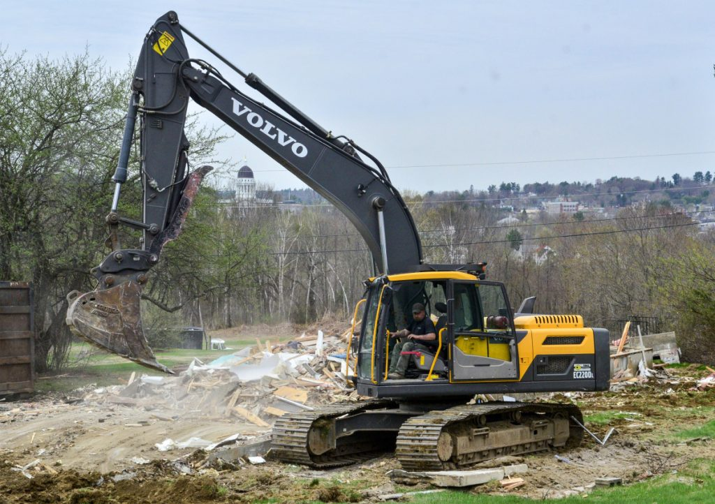An excavator operator cleans up on Thursday after demolishing one of two houses on Independence Drive in Augusta.