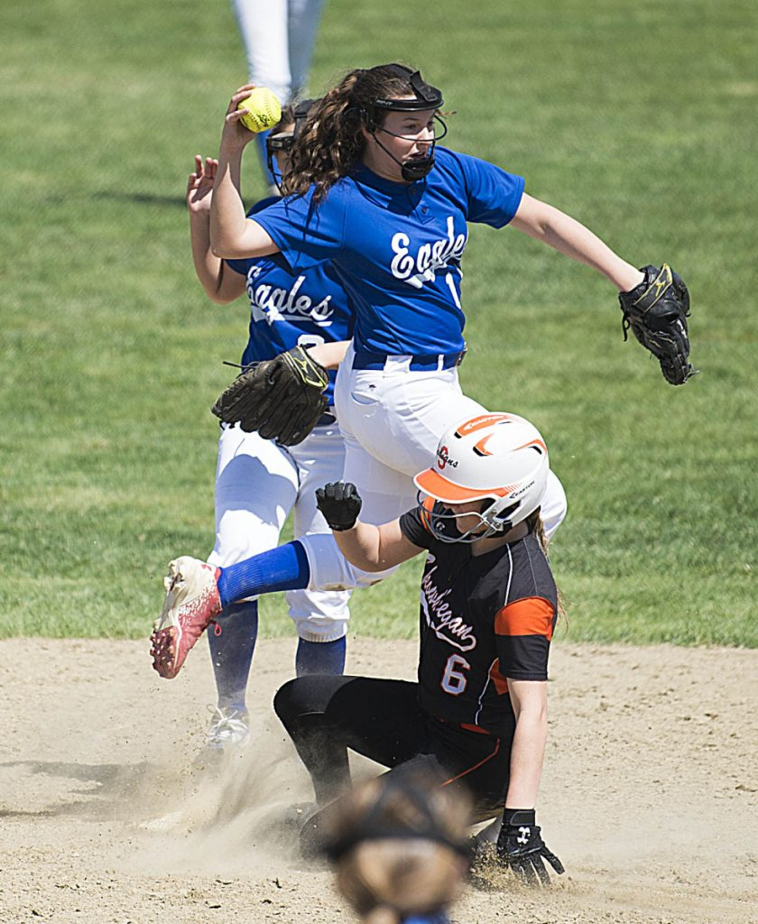 Messalonskee shortstop Taylor Baker, center, leaps over Skowhegan's Sydney Ames (6) as she tries to turn the double play Saturday in Skowhegan.