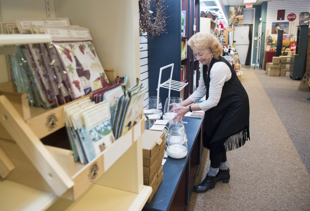 Carla Dumont sets up merchandise at the new location of Maine Made and More at The Concourse in downtown Waterville on Friday.