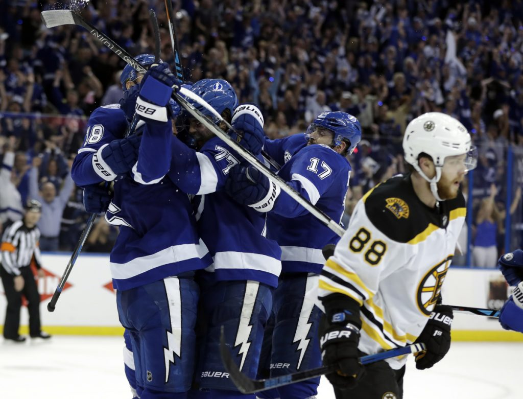 Tampa Bay Lightning defenseman Anton Stralman, left, is mobbed by teammates after scoring against the Boston Bruins during the third period of Game 5 of a second-round playoff series Sunday in Tampa, Florida.