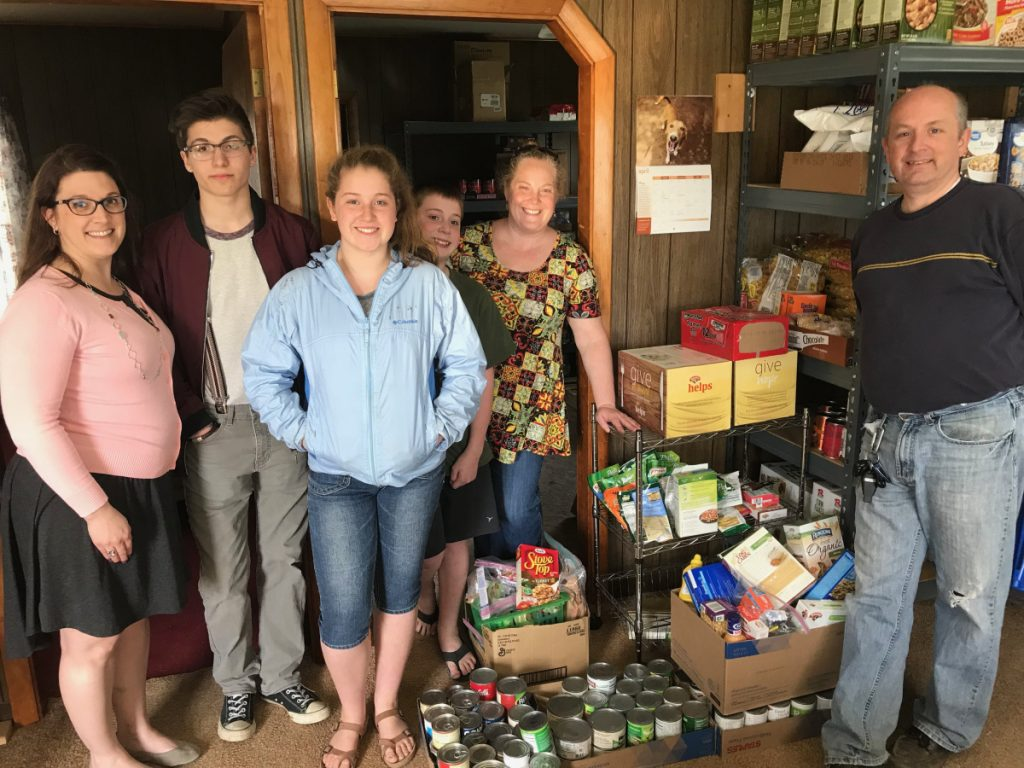Snow Pond Arts Academy students. from left, Jess Crowell, Ethan Michaud, Kiara Hurley, Donovan Hurley, Melissa Hurley and Brian Hurley recently delivered 12 cases of food they collected during Spirit Week to the Sidney Food Bank located on West River Road in Sidney.