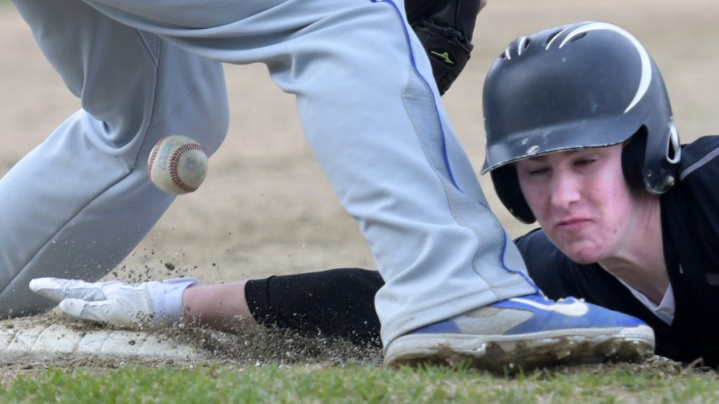Maranacook's Jarred Schmidt slides into third base beneath a throw to Lawrence's Michenzie Steeves during a Kennebec Valley Athletic Conference game Monday in Readfield.