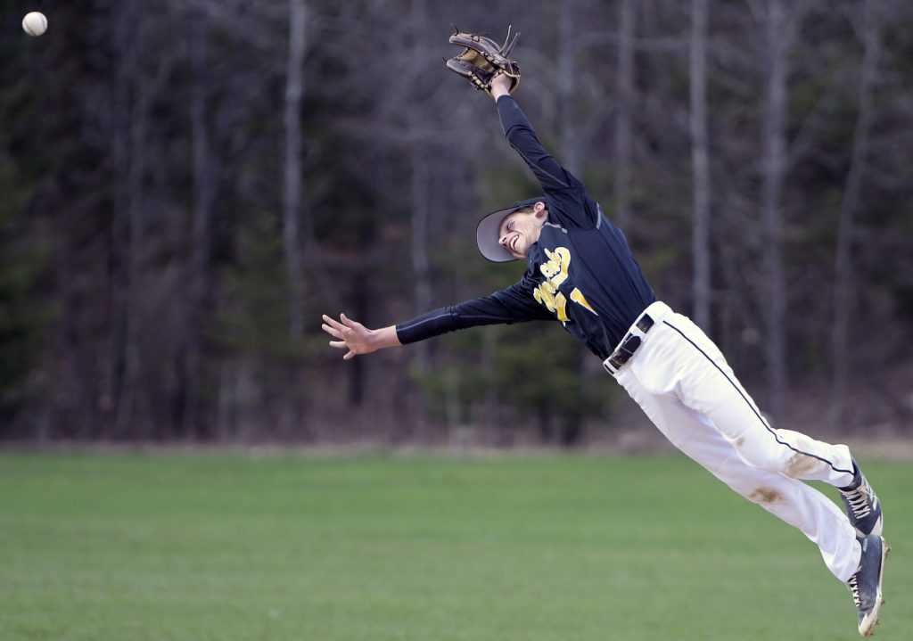 Maranacook's Wyatt Lambert gets some air time jumping for a line drive against Lawrence during a Kennebec Valley Athletic Conference game Monday in Readfield.