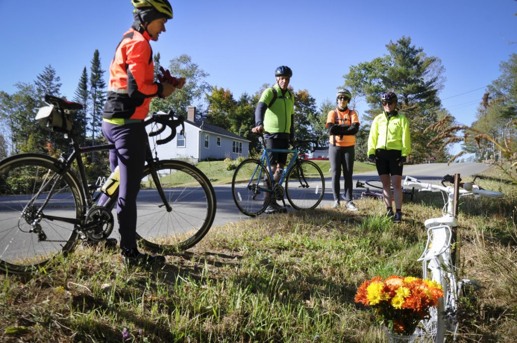 "Bicycle Coalition of Maine Executive Director Nancy Grant, left, joins other bicyclists in paying respect to Dr. Carol Eckert in October 2017. Eckert died from injuries suffered in October 2016 when a pickup truck hit her while she was riding near her home in Windsor. The bicycle was painted white, as a ""ghost bike,"" and placed at the site of the accident on Wingood Road."