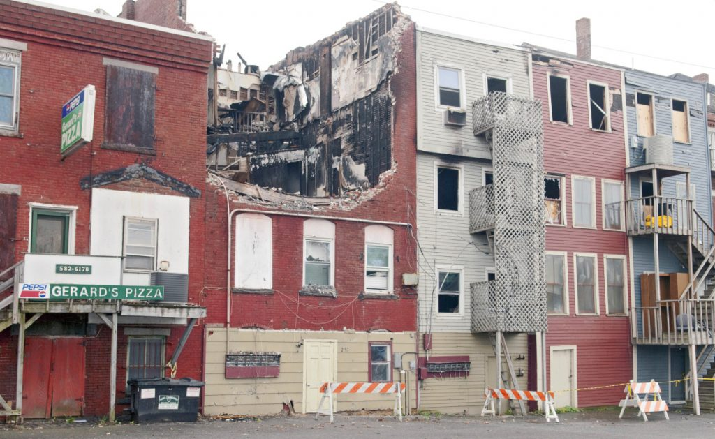 The collapsed roof on 235 Water St. in Gardiner is seen Oct. 22, 2015, after the building was heavily damaged by a fire earlier that year. Gardiner officials are considering declaring the buildings dangerous after its new owner has done nothing to it.