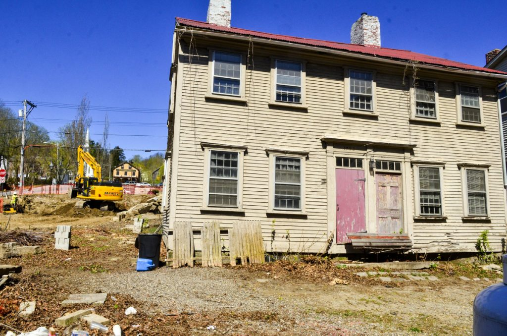 Workers from MainEx dig a basement hole at the corner of the Central and Second streets on May in Hallowell. The Dummer House, in background, will be moved there in a few weeks and the space on Dummer's Lane will become parking.