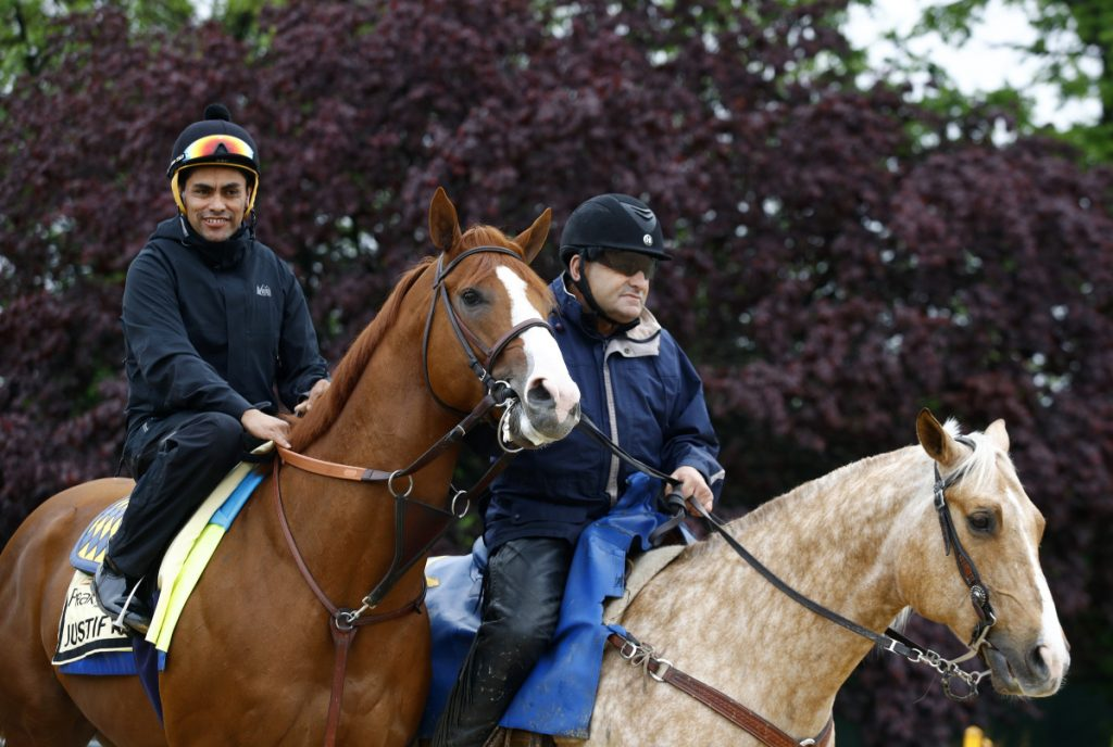 Kentucky Derby winner Justify, left, with exercise rider Humberto Gomez aboard, is escorted to the track for a workout Thursday at Pimlico Race Course in Baltimore. The Preakness Stakes is scheduled to take place Saturday.