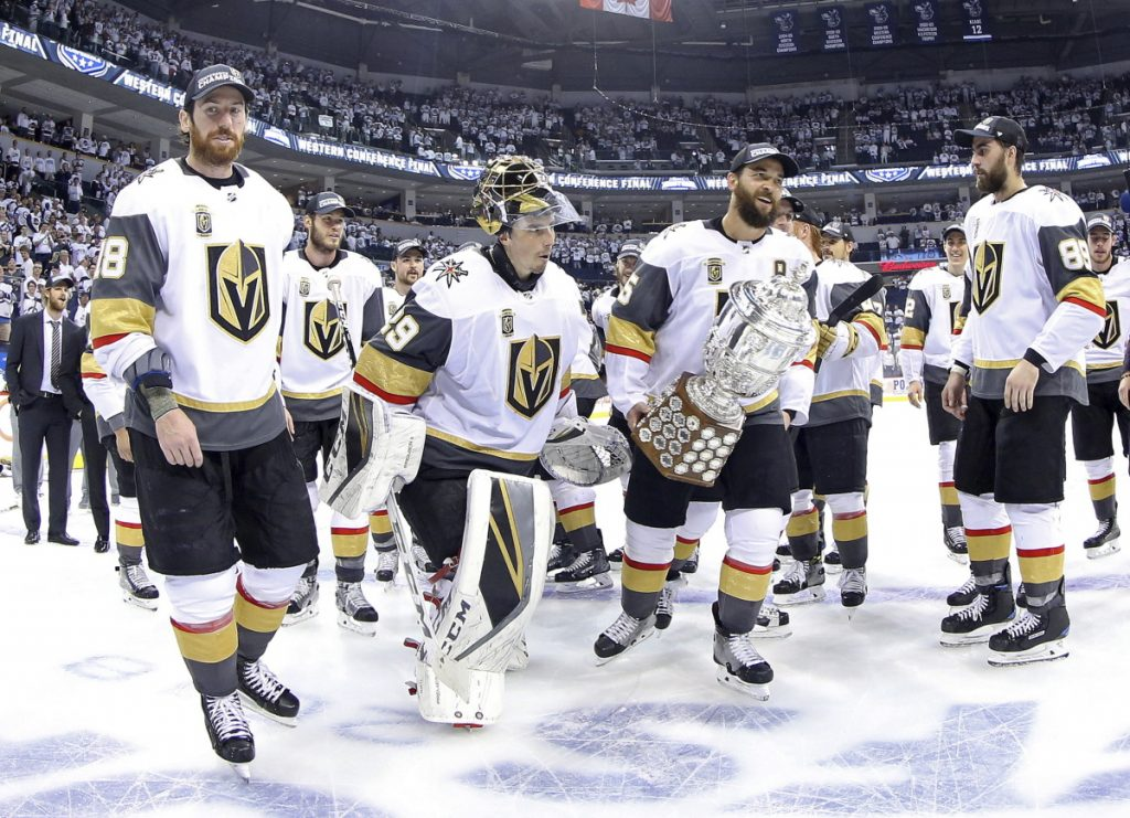 Vegas Golden Knights players James Neal (18), Deryk Engelland (5), goaltender Marc-Andre Fleury (29) and the rest of the team celebrate after defeating the Winnipeg Jets during Western Conference Finals on Sunday in Winnipeg.