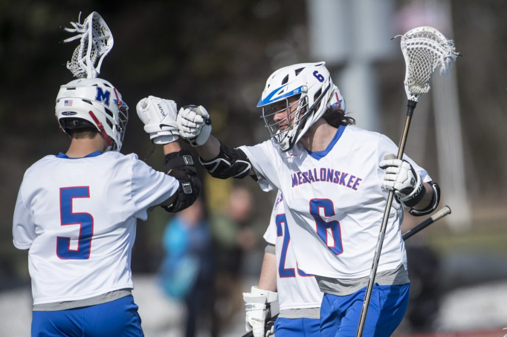 Messalonskee's Matt Trembly (6) center celebrates a goal with teammate Chase Warren (5) in the first half of an April 24 game against Gardiner at Thomas College.