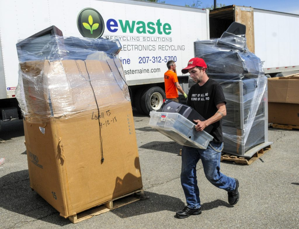 Volunteer Brad Hanley carries a tote of old computers during an e-waste recycling event on Saturday in the Augusta Civic Center parking lot. People made donations to drop off items and the event was a fundraiser for Bridging The Gap, which runs the Augusta Warming Center, Addie's Attic and Basic Essentials Pantry. The group wants to move its social services to the Emmanual Lutheran Episcopal Church on Eastern Avenue in Augusta.