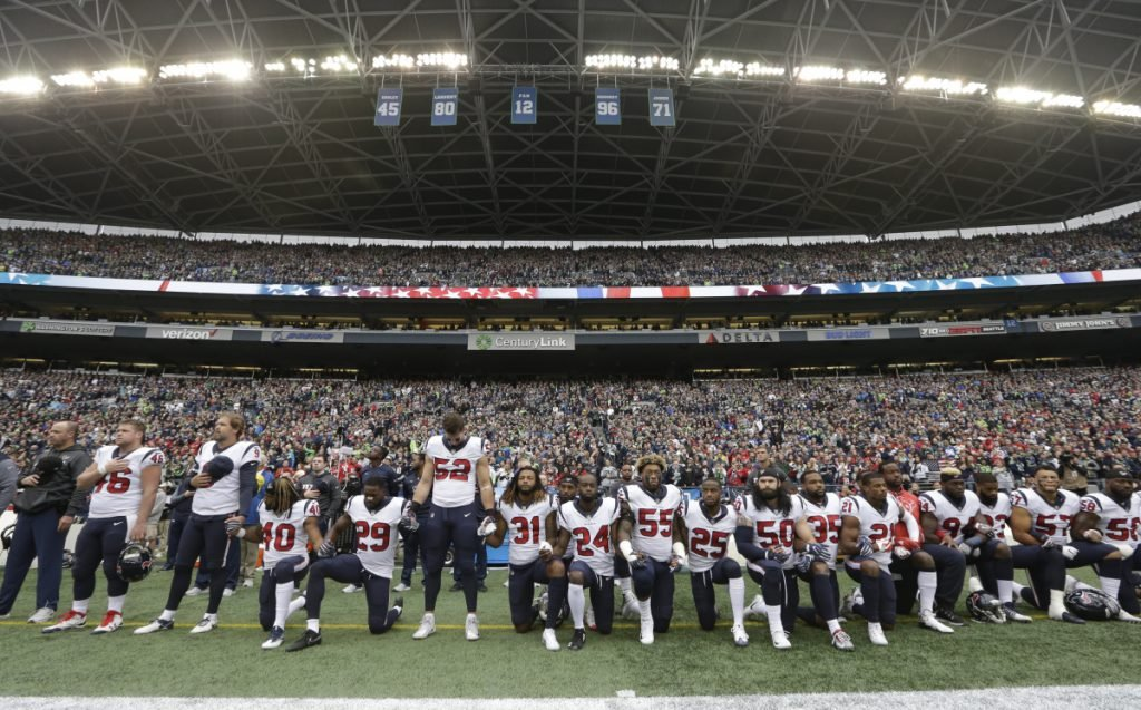 "In this October 2017 photo, Houston Texans players kneel and stand during the singing of the national anthem before a game against the Seattle Seahawks in Seattle. NFL owners have approved a new policy aimed at addressing the firestorm over national anthem protests, permitting players to stay in the locker room during the ""The Star-Spangled Banner"" but requiring them to stand if they come to the field. The decision was announced Wednesday by NFL Commissioner Roger Goodell during the league's spring meeting in Atlanta."