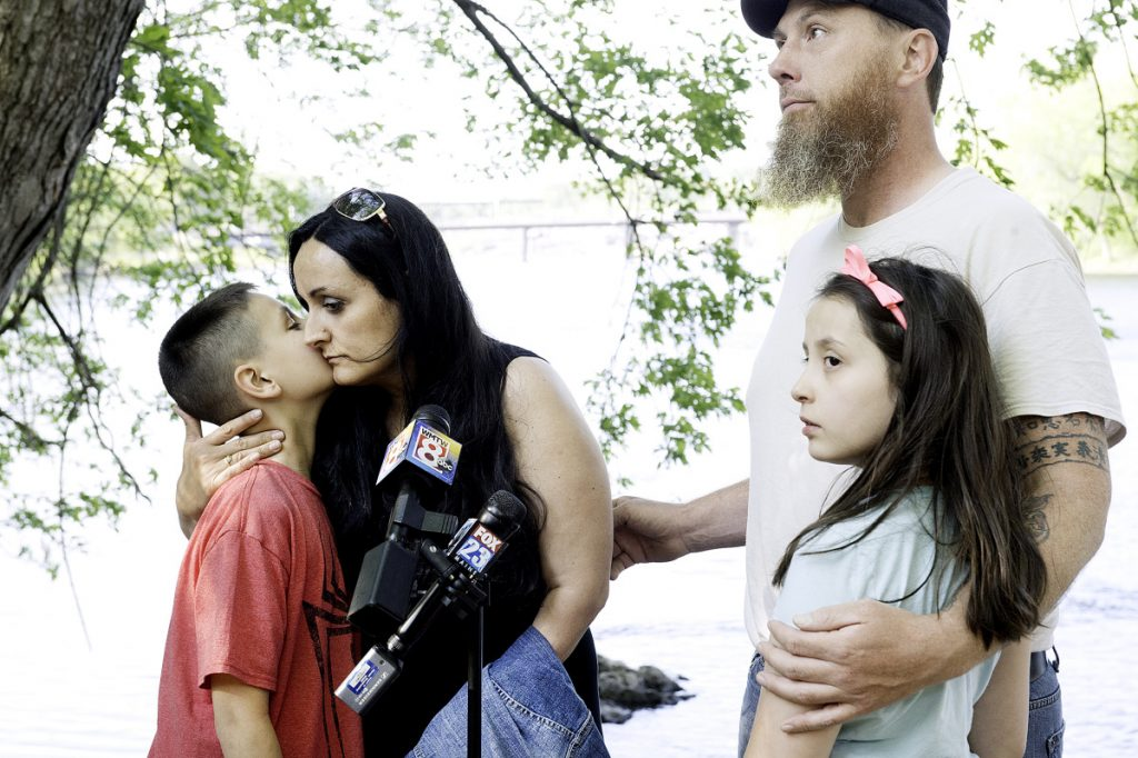 Maxim McFarland, 10, gives his mother, Helena Gagliano-McFarland, a kiss while his father, Jason McFarland, holds his sister, Giada, 9, on the side of the Androscoggin River in Auburn on Wednesday. Maxim and his brother, Valerio, fell into the river April 24. Maxim was rescued soon after while his 5-year-old brother's body was found nearly three weeks later.