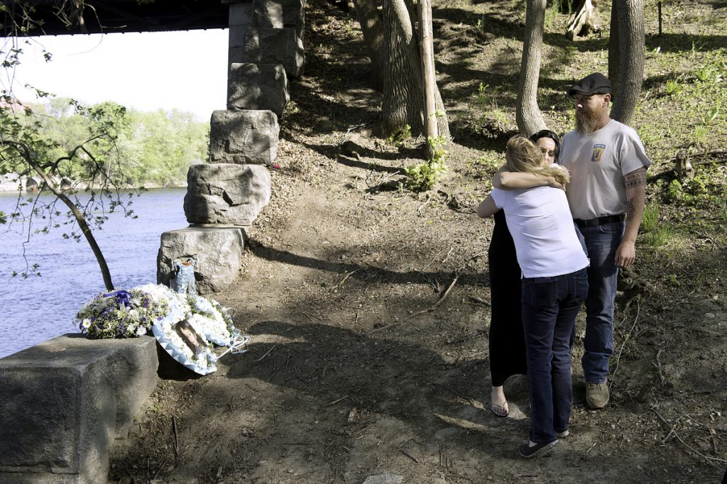 Helena Gagliano-McFarland gets a hug from Kelly Henry near where McFarland's 5-year-old son, Valerio, fell into the Androscoggin River in Auburn. McFarland's husband and Valerio's father, Jason, is at right. Henry said she became friends with the family as the three-week search for Valerio's body played out.