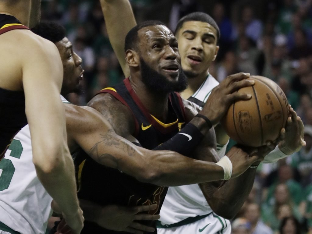 Cleveland Cavaliers forward LeBron James drives against Boston Celtics guard Marcus Smart, left, and forward Jayson Tatum, right, during the first quarter of Game 5 of the Eastern Conference Finals on Wednesday in Boston.