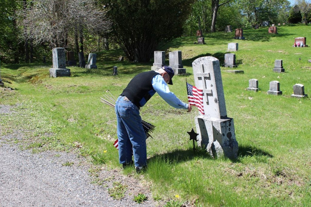 Bud Smith, 92, of Farmingdale, places American flags on Monday on the graves of veterans for the town of Farmingdale, many of whom he served with during World War II.
