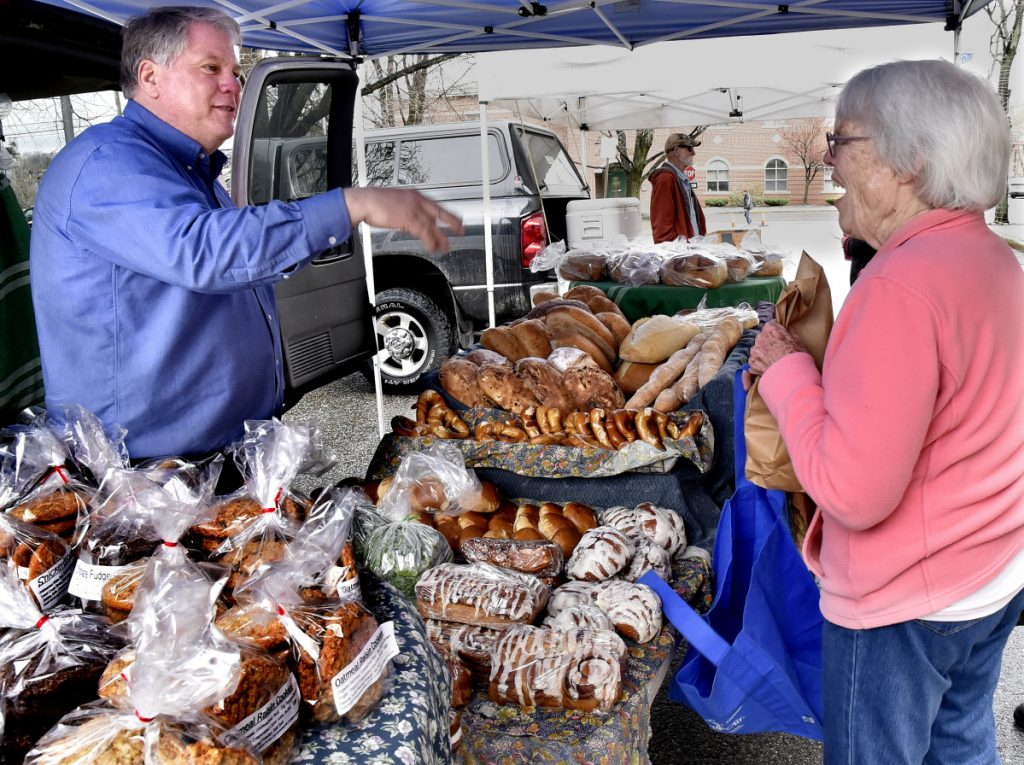 One of the legacies of Waterville Main Street is the Downtown Waterville Farmers' Market, which opened for the season on Common Street on April 26, 2018. Karl Rau of Good Bread speaks with customer Kathleen Bammer on opening day.