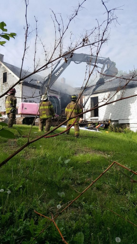 An excavator knocks down the front of the home at 114 Belgrade Road Sunday morning, as firefighters attack the fire that broke out there around 4 a.m.