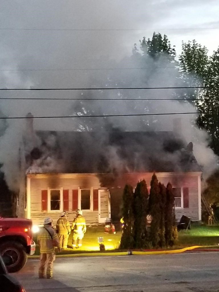 Smoke billows from the home at 114 Belgrade Road early Sunday morning. Neighbors say they were awakened around 4 a.m., to find the home of their neighbors, Kevin and Allison Sanborn, on fire. They say the Sanborns, their two sons and pets were able to get out of the home.