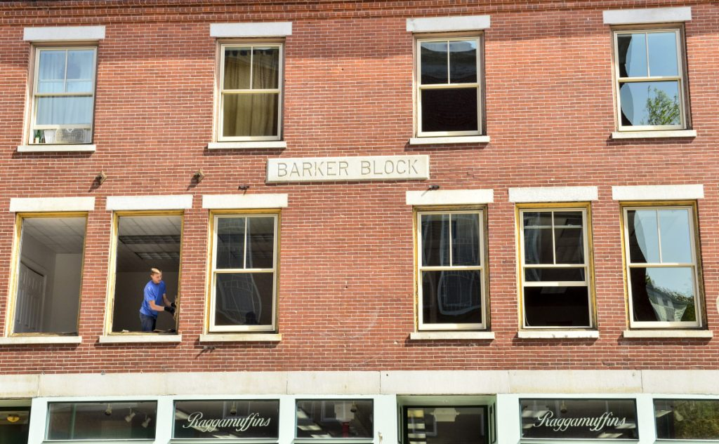 Kaleb Burbank, of Jacob's Glass, tears out the frames of old windows to install new Pella replacement windows in second floor office about Ragamuffin's on May 16 along the one way section of Water Street in downtown Gardiner.
