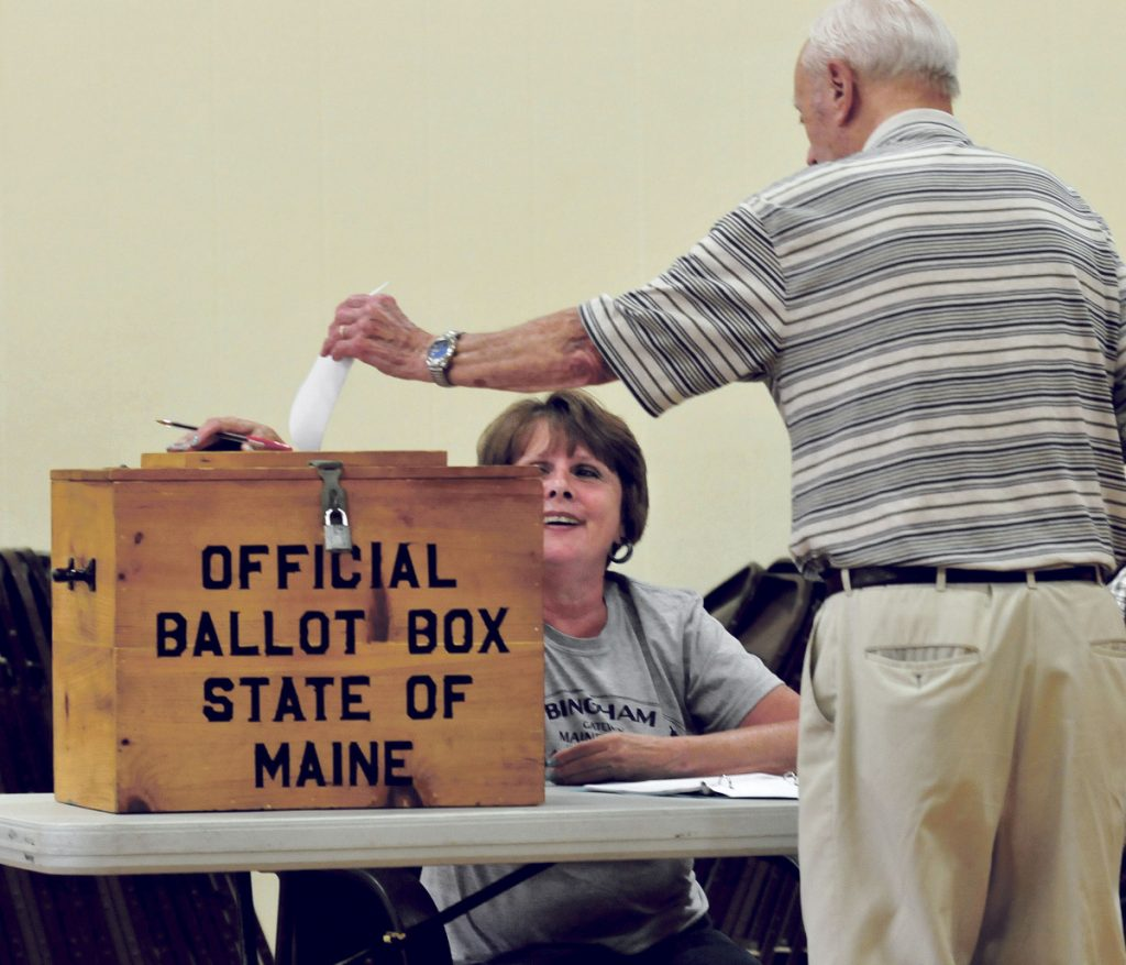 Last year's SAD 13 budget weathered four votes before it passed. Stanley Redmond casts his ballot as clerk Liz Brochu looks on during voting at the Quimby School in Bingham on July 25, 2017.