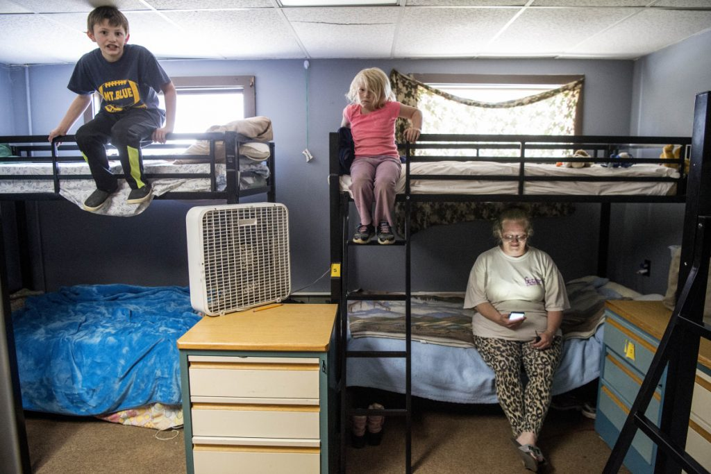 Jennifer Sweetster, bottom right, looks at her phone from her bunk as her daughter Hannah Chapman, 5, top right, and son Keith Chapman, 9, left, sit on their bunks at the Western Maine Homeless Outreach shelter in Farmington on Wednesday.
