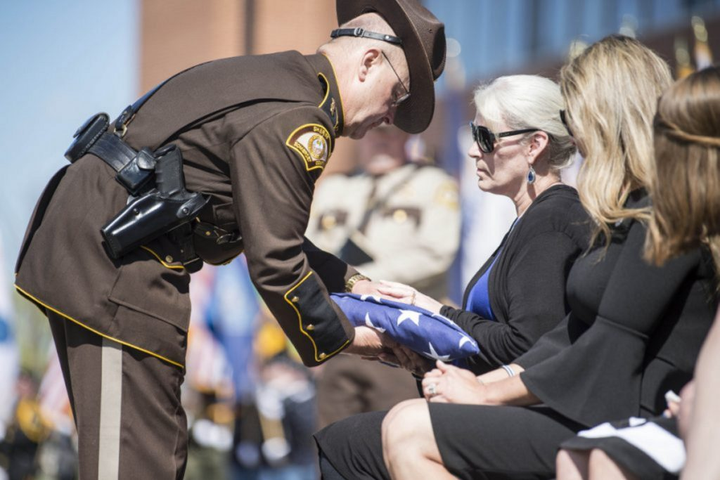 Somerset County Sheriff Dale Lancaster offers a folded American flag to Sheryl Cole, wife of Cpl. Eugene Cole, during funeral services at the Cross Insurance Center in Bangor on May 7.
