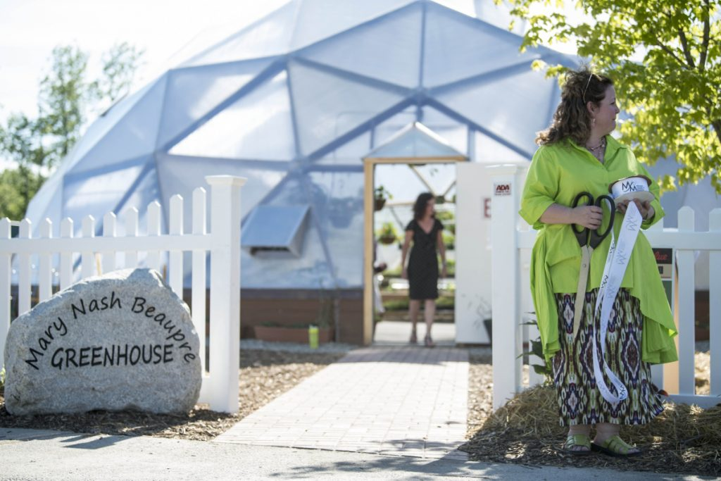 Crista Lavenson stands outside the gates to the new Mary Nash Beaupre Greenhouse at the ceremony marking the opening of the new addition at the Alfond Youth Center on North Street in Waterville on Wednesday.