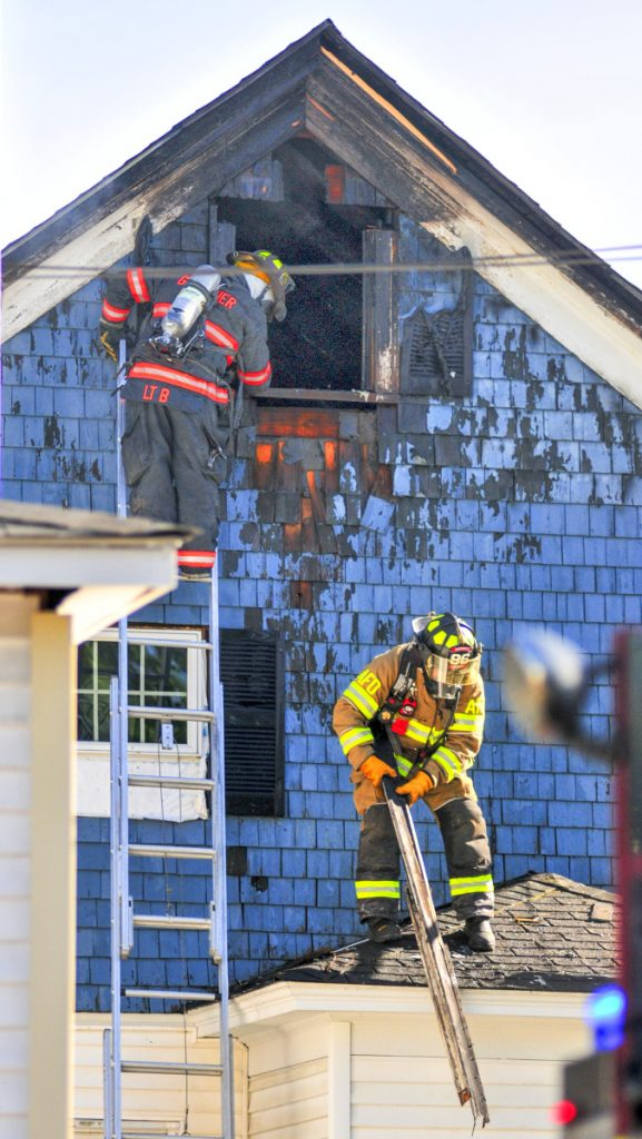Firefighters pull off boards to expose fire underneath them at 79 Willow St. in Augusta on Wednesday.