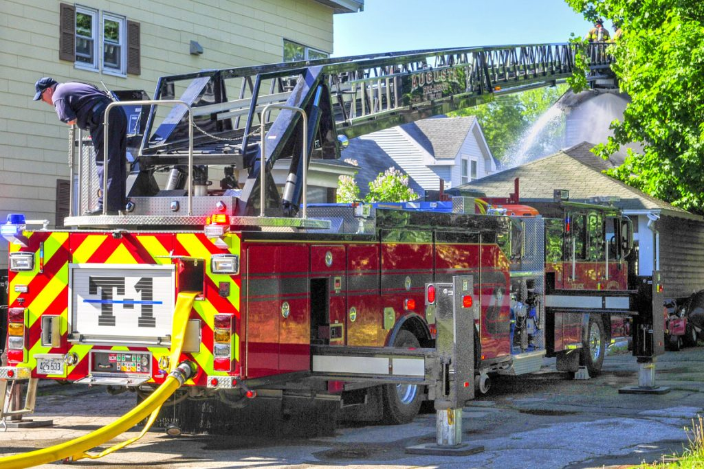Firefighters on Augusta tower truck 1, parked on Myrtle Street, spray water onto the backside of 79 Willow St. in Augusta on Wednesday.