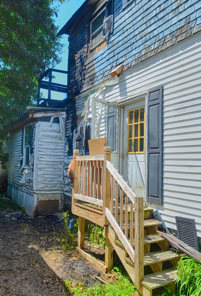 Damage can be seen on the back deck of 79 Willow St. in Augusta, a day after a fire burned an apartment building there.
