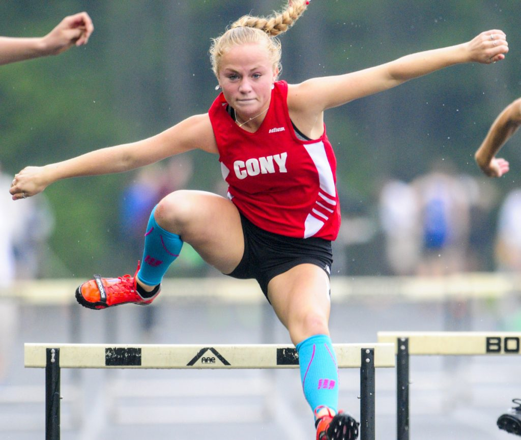 Cony's Anna Reny runs the 300-meter hurdles during a rainy Kennebec Valley Athletic Conference track and field championships last Saturday in Topsham.