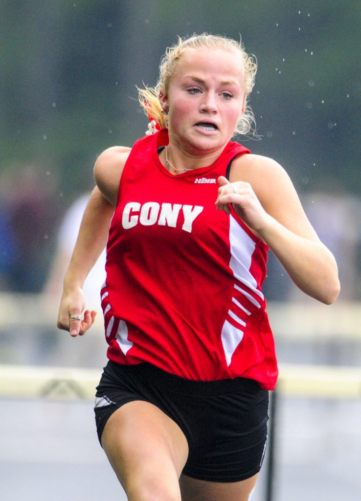 Cony's Anna Reny runs the 300-meter hurdles during a rainy Kennebec Valley Athletic Conference track meet last Saturday at Mt. Ararat High School in Topsham.