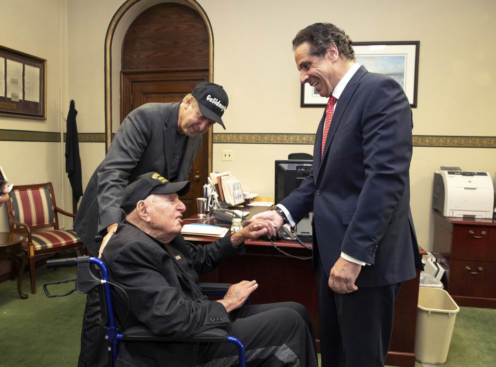 In this photo provided by the Office of the Governor of New York, Governor Andrew M. Cuomo, right, shakes hands with World War II veteran Sidney Walton at the Capitol in Albany, N.Y., Friday, May 18, 2018. The 99-year-old World War II veteran who regretted skipping the chance to meet some of the nation's last Civil War veterans in 1940 is on a mission to visit all 50 states so people who've never met a WWII vet can finally meet one. Standing at left is Walton's son, Paul Walton.
