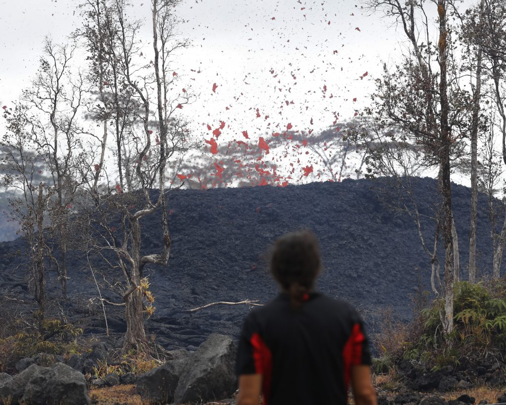 Abe Pedro watches lava shoot out of a fissure on Pohoiki Road, Friday, near Pahoa, Hawaii. Hawaii residents covered their faces with masks after a volcano menacing the Big Island for weeks exploded, sending a mixture of pulverized rock, glass and crystal into the air in its strongest eruption of sandlike ash in days.