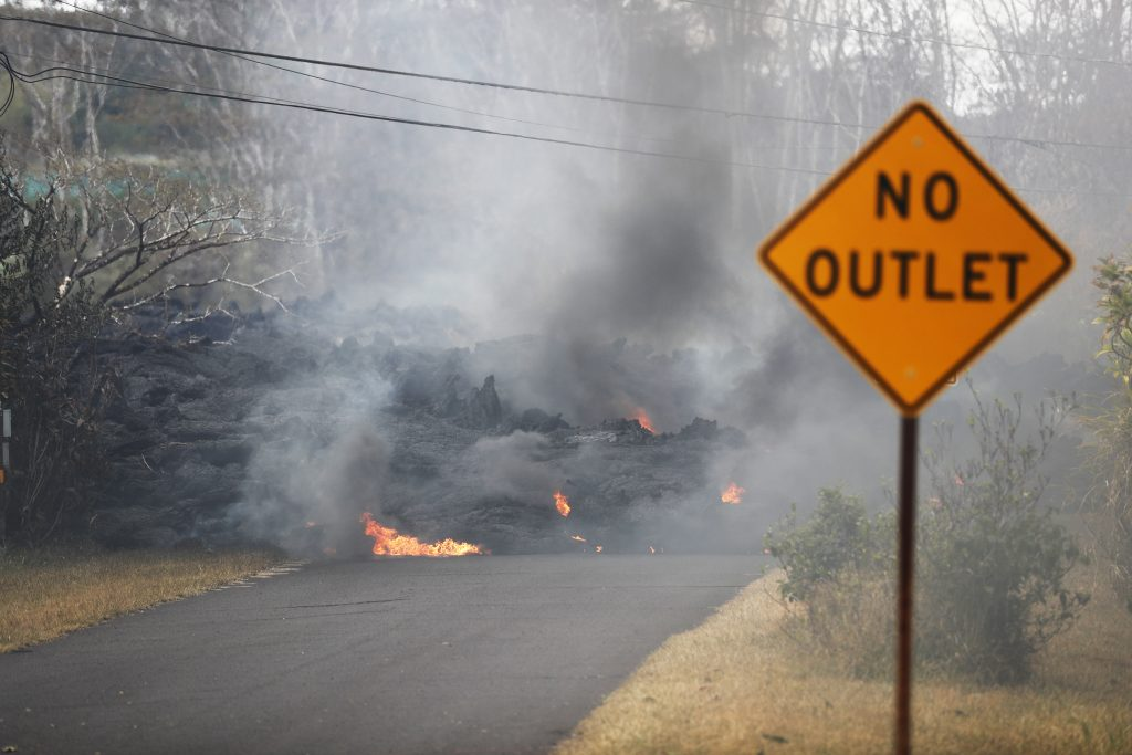 Lava crosses the road near Pohoiki Road, Friday near Pahoa, Hawaii. Hawaii residents covered their faces with masks after a volcano menacing the Big Island for weeks exploded, sending a mixture of pulverized rock, glass and crystal into the air in its strongest eruption of sandlike ash in days.