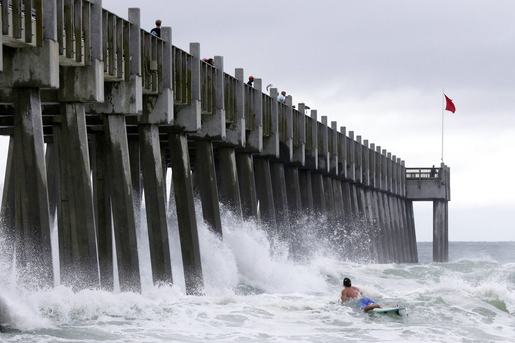 A surfer makes his way out into the water as a subtropical approaches on Monday in Pensacola, Fla.    Dan Anderson/Associated Press