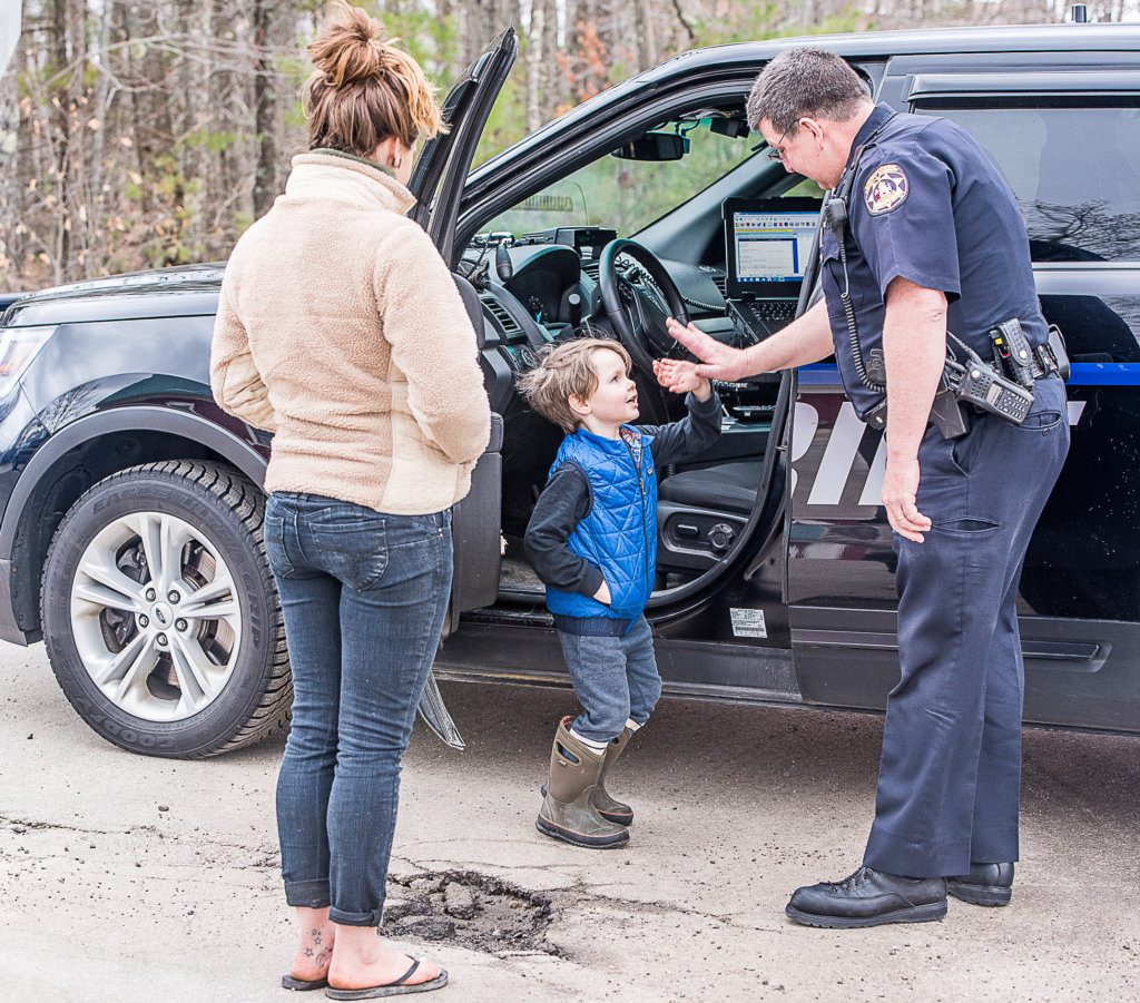 Androscoggin County Sheriff's Deputy Dennis Sampson gives a low-five to 5-year-old Sebastian Coron in Poland last Monday. Left is Angela, Sebastian's mother, asking Sampson about a fire on Cobb Road.