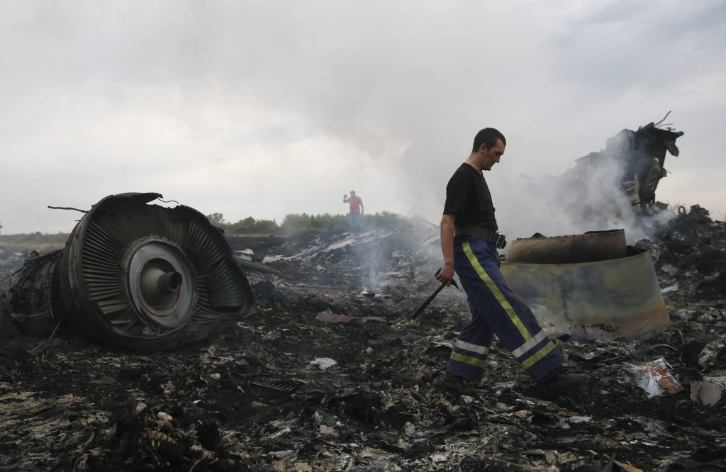 An emergency responder examines the site of the Malaysia Airlines Boeing 777 plane crash near the settlement of Grabovo in the Donetsk region of Ukraine on July 17, 2014.