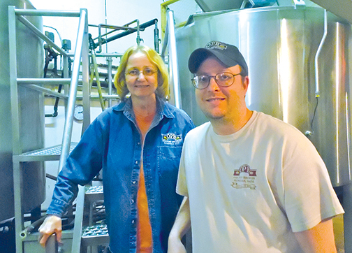 Nancy Chandler and son, Adam Chandler, in front of brewing tanks at Oak Pond Brewing Company in Skowhegan. Susan Varney photo