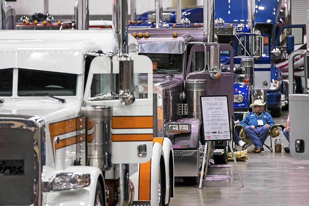 """A truck owner sits by his custom rig among entrants in the """"Pride and Polish"""" competition during the 16th annual Great American Trucking Show in Dallas in 2014."""