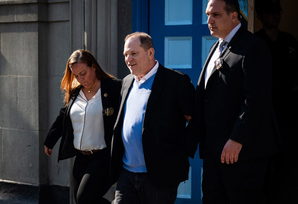 Harvey Weinstein is escorted in handcuffs out of the New York Police Department's 1st Precinct on Friday after surrendering to face charges in sexual assault cases involving two women.